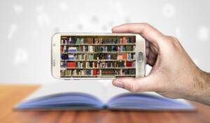 A cell phone with bookshelves on the display with an open book in the background